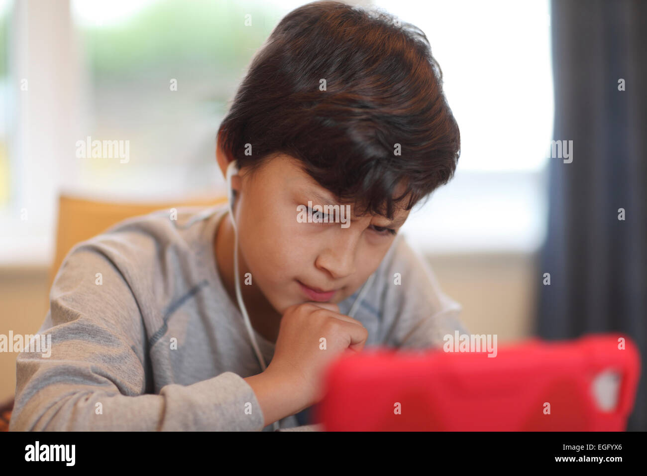 Young frowning boy playing with tablet computer - Stock Image
