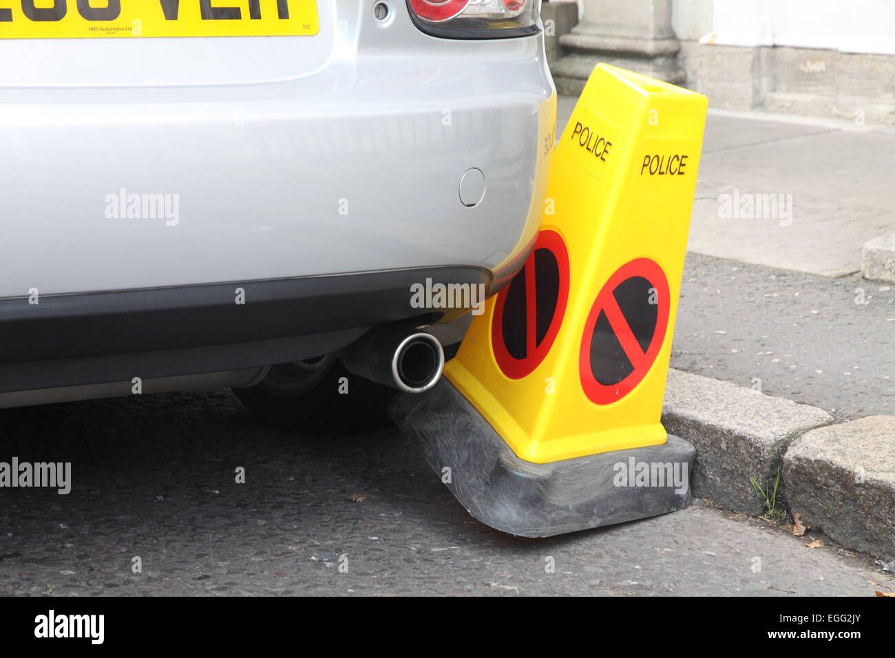 Car badly parked against a Police No Parking cone - Stock Image