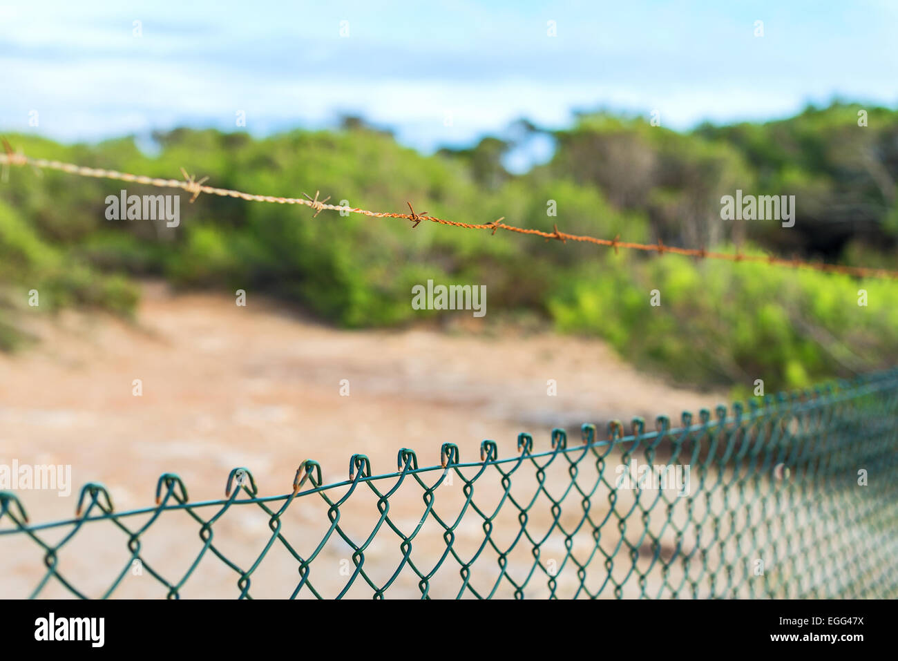 Fence with barbed wire under blue sky. - Stock Image