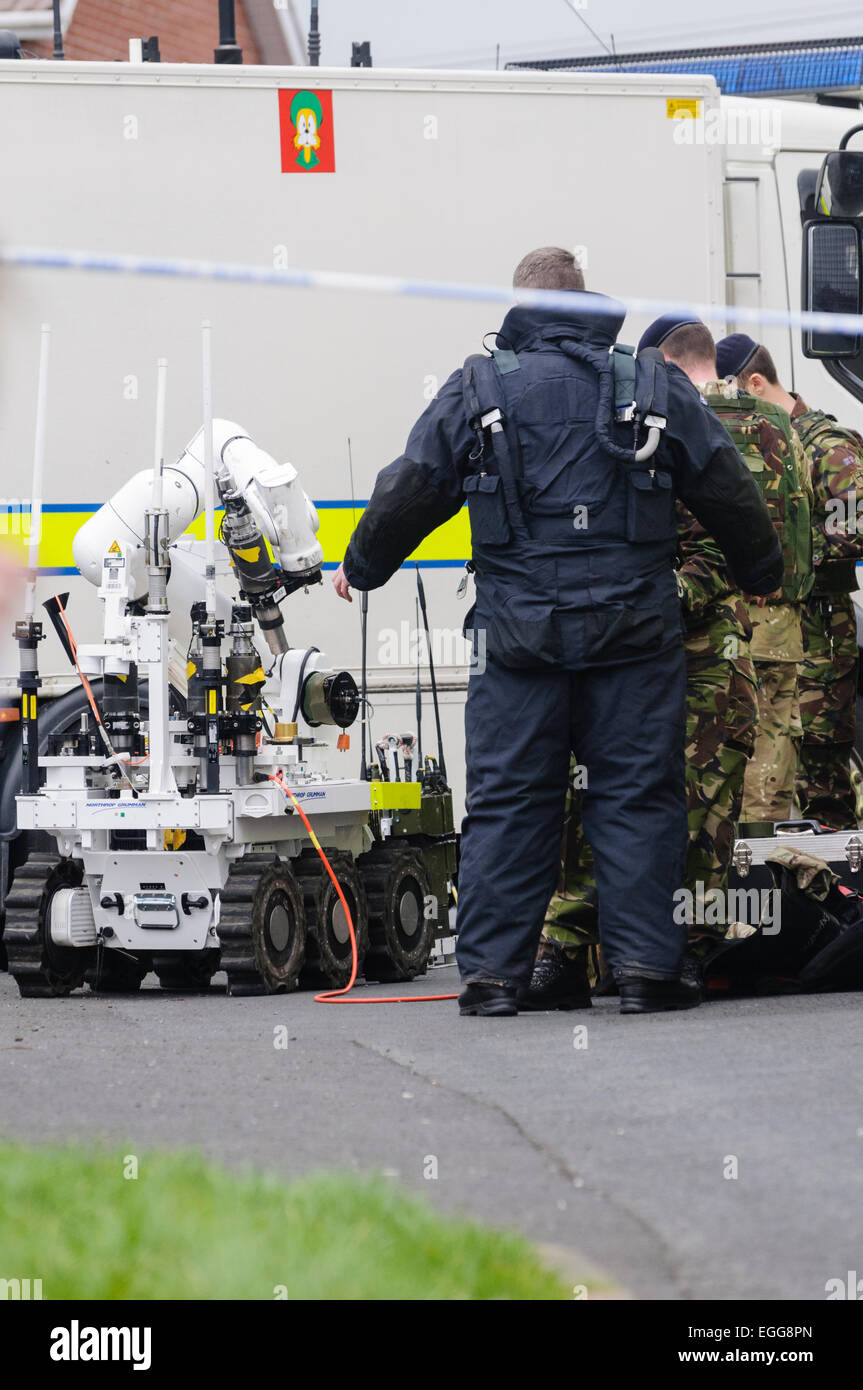 Ammunition Technical Officer dons a bomb-proof suit prior to examining a pipe bomb, left on a car in Northern Ireland - Stock Image