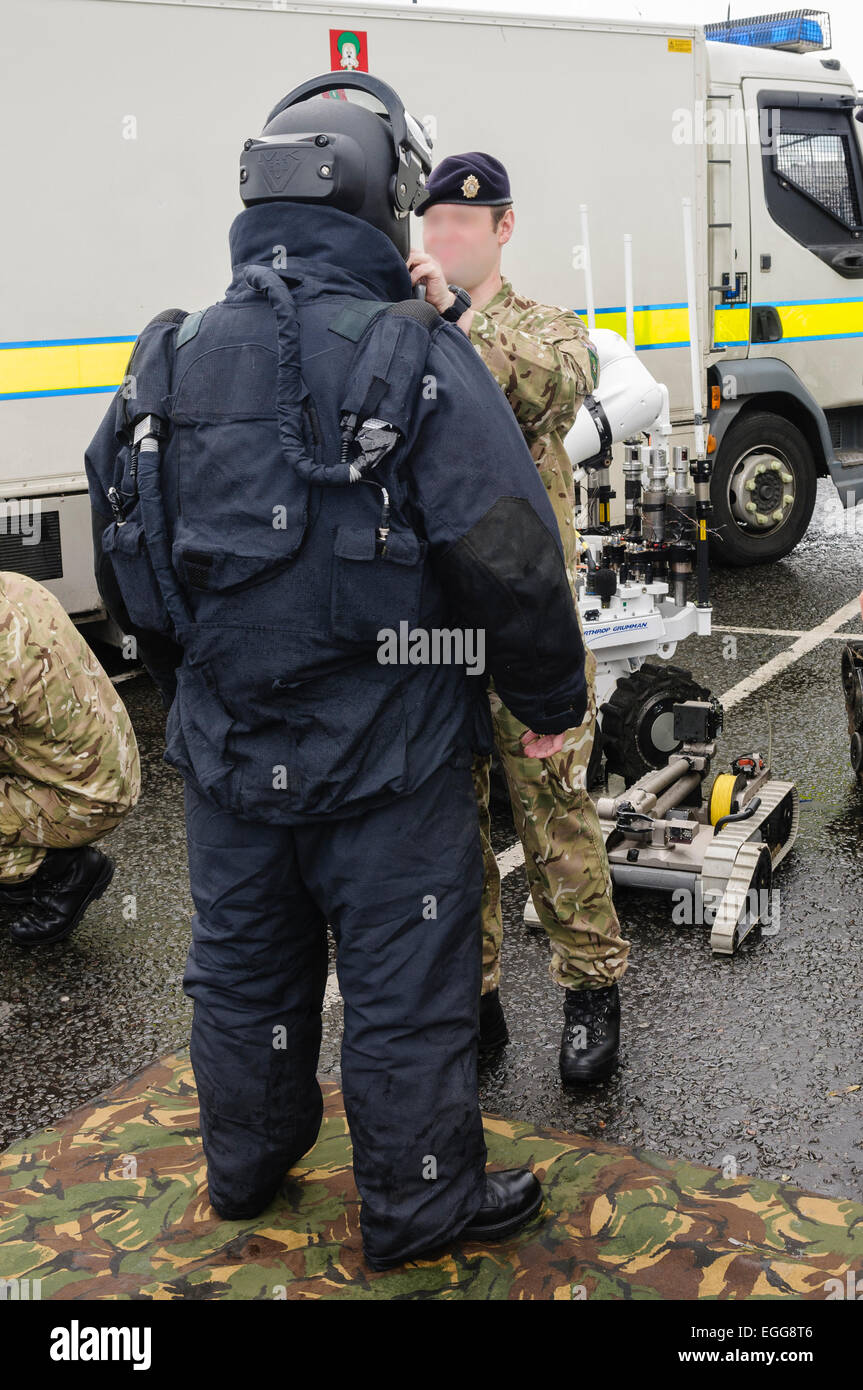 Ammunition Technical officer wearing a bomb-proof suit prepares to defuse a bomb left on a car in Northern Ireland - Stock Image