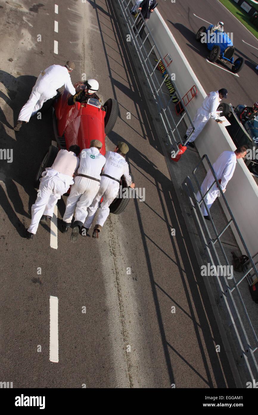 Mechanics pushing a failing car back to their pit / Goodwood Revival / Goodwood / UK - Stock Image