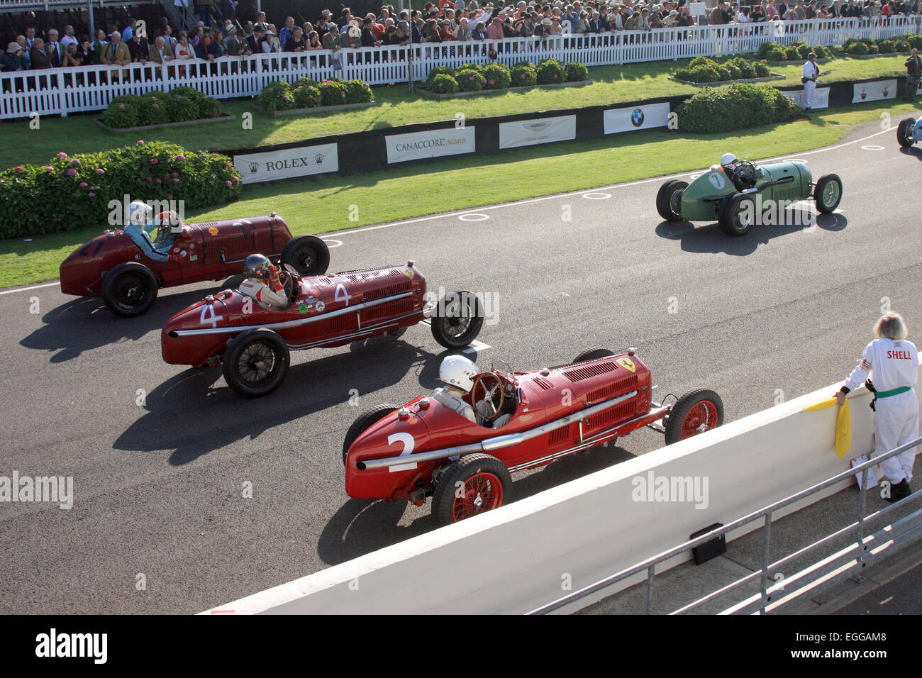 A mouth-watering starting grid with Umberto Rossi's bright red 1934 Alfa Romeo Tipo B nearest the camera / Goodwood - Stock Image