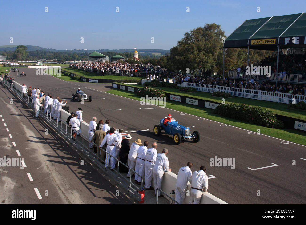 Pit crews line the track in the sunshine as Ludovic Lindsay passes in his blue 1936 ERA B-type R5B 'Remus' - Stock Image