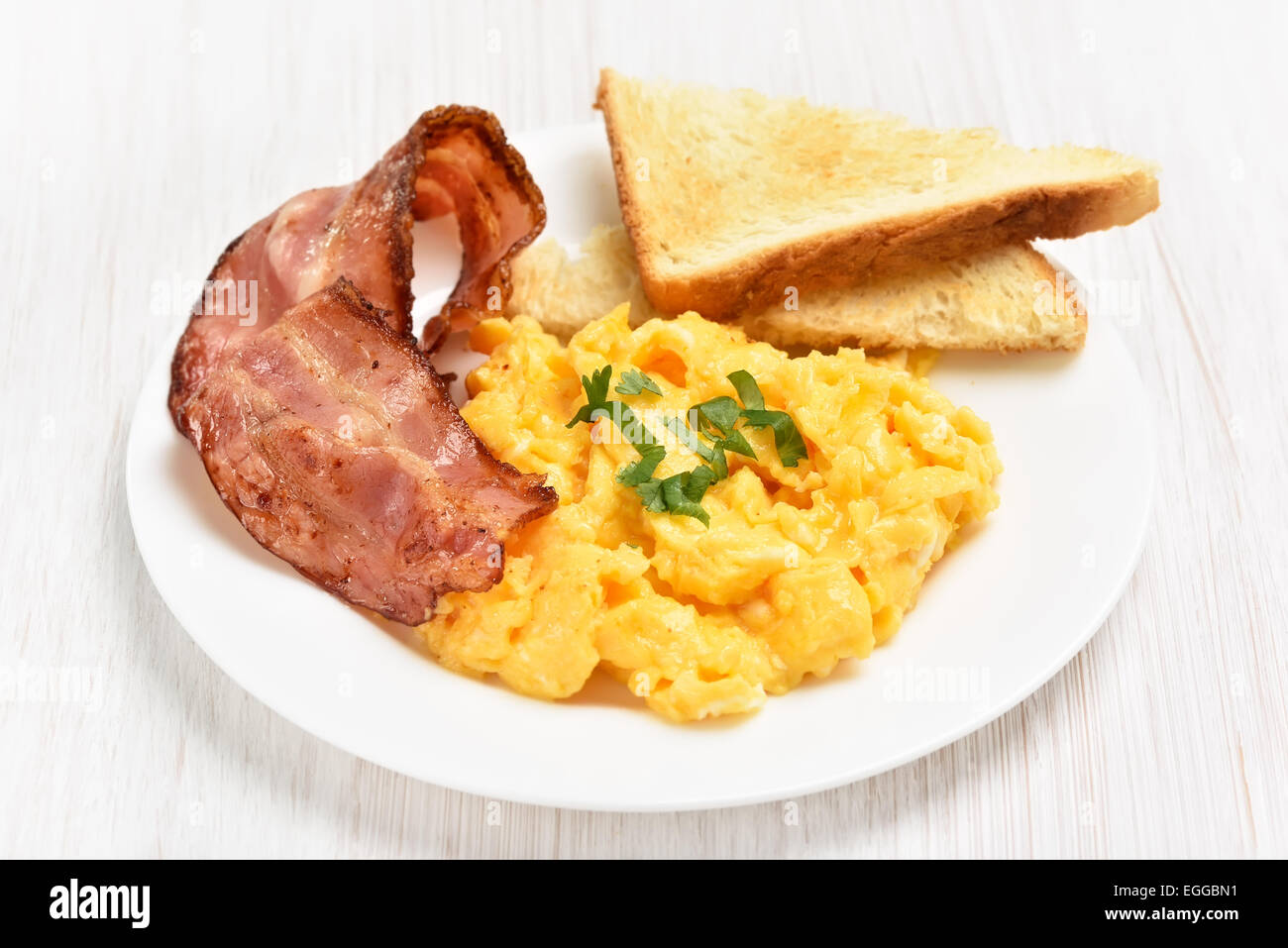 Scrambled eggs with bacon and toasts on white plate, close up view - Stock Image