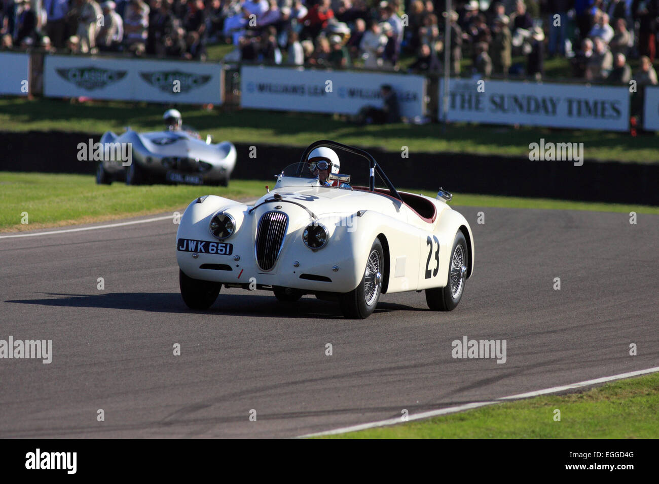 1950 Jaguar XK120 driven by Stephen Bond emerging from Madgwick Corner / Goodwood Revival / Goodwood / UK - Stock Image