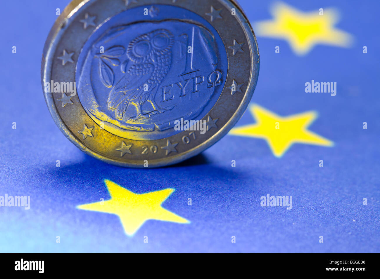 Greek one Euro coin on EU-flag - Stock Image