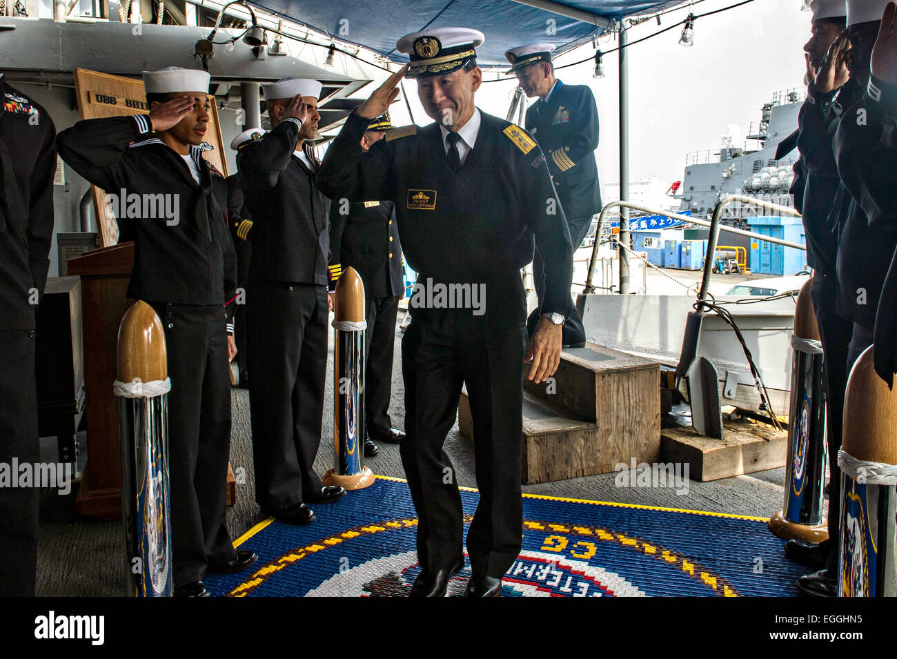 Japan Maritime Self Defense Force Rear Adm. Umio Otsuka is welcomed aboard the U.S. Navy Ticonderoga-class guided Stock Photo