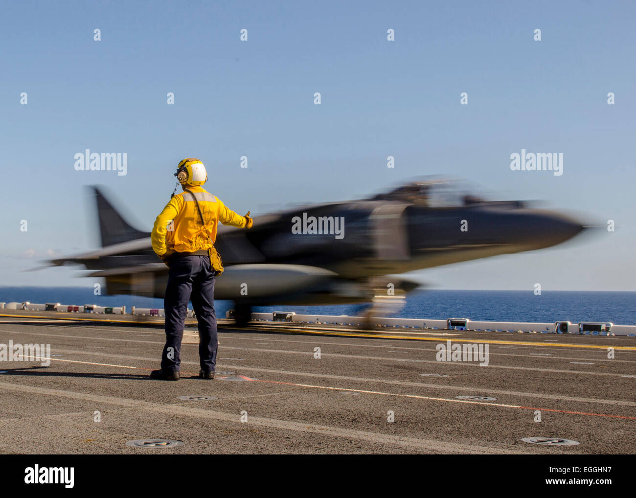 A US Navy sailor signals take off for a AV-8B Harrier fighter jet from the flight deck of the new amphibious assault - Stock Image