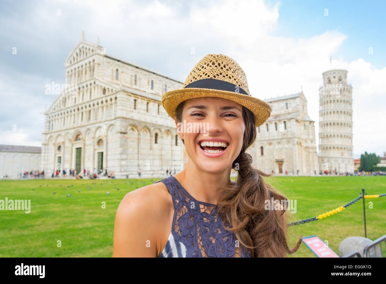 Portrait of happy young woman on piazza dei miracoli, pisa, tuscany, italy Stock Photo