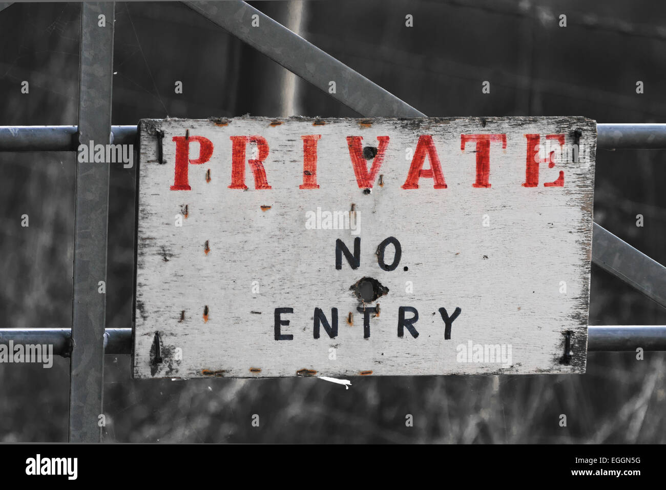 private no entry sign on metal gate with prominent red and black letters on white standing out against monochrome Stock Photo
