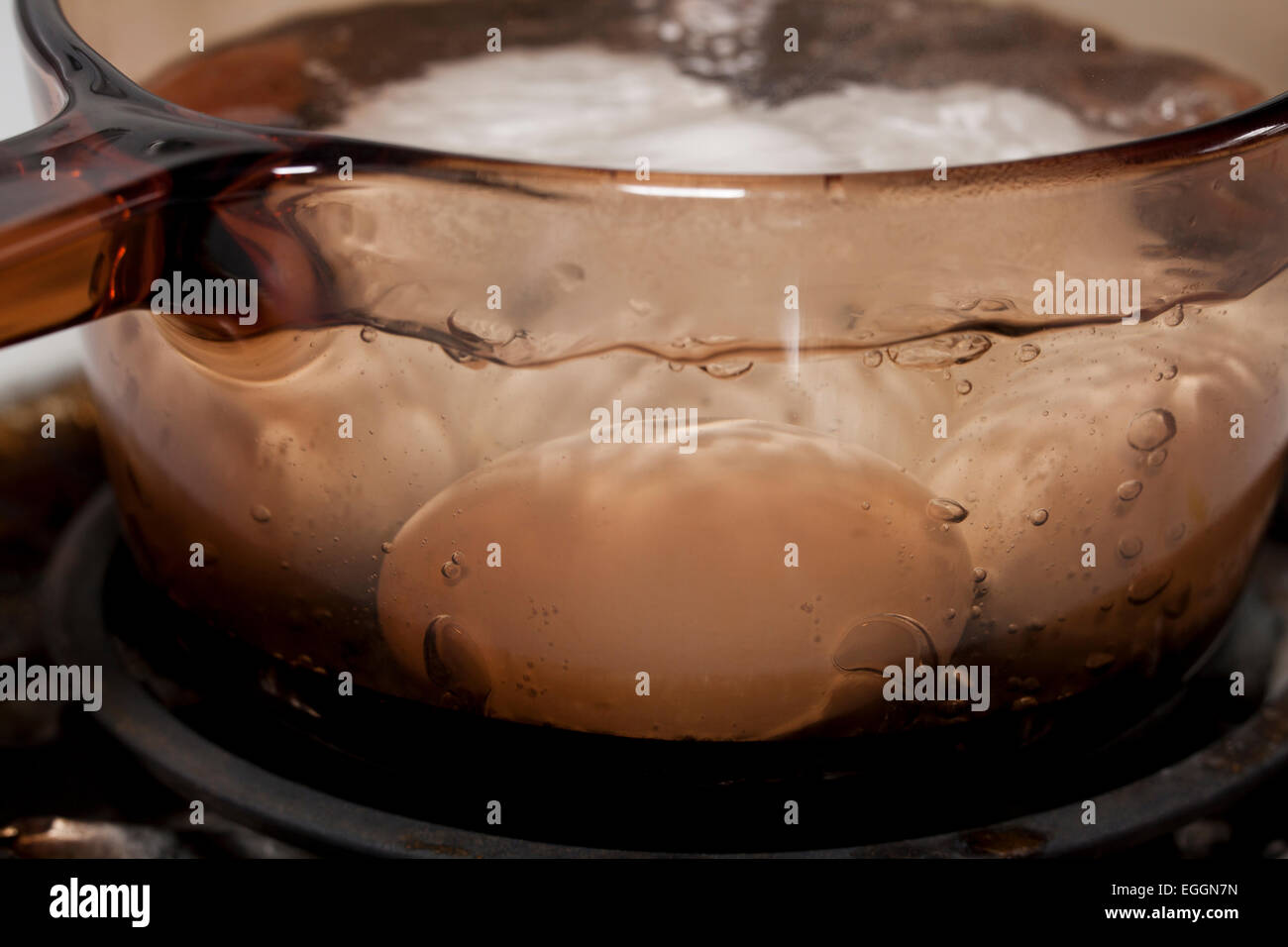 Eggs boiling in Pyrex pot - USA - Stock Image