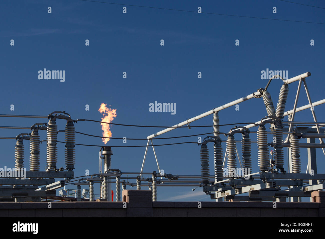 Denver, Colorado - A flare burns off gas at near electrical equipment at Suncor Energy's oil refinery. - Stock Image