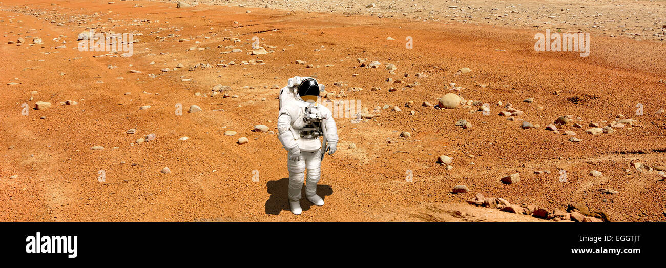 A marooned astronaut looks up at an alien sun that illuminates the barren world he stands on. Rocks and iron rich - Stock Image