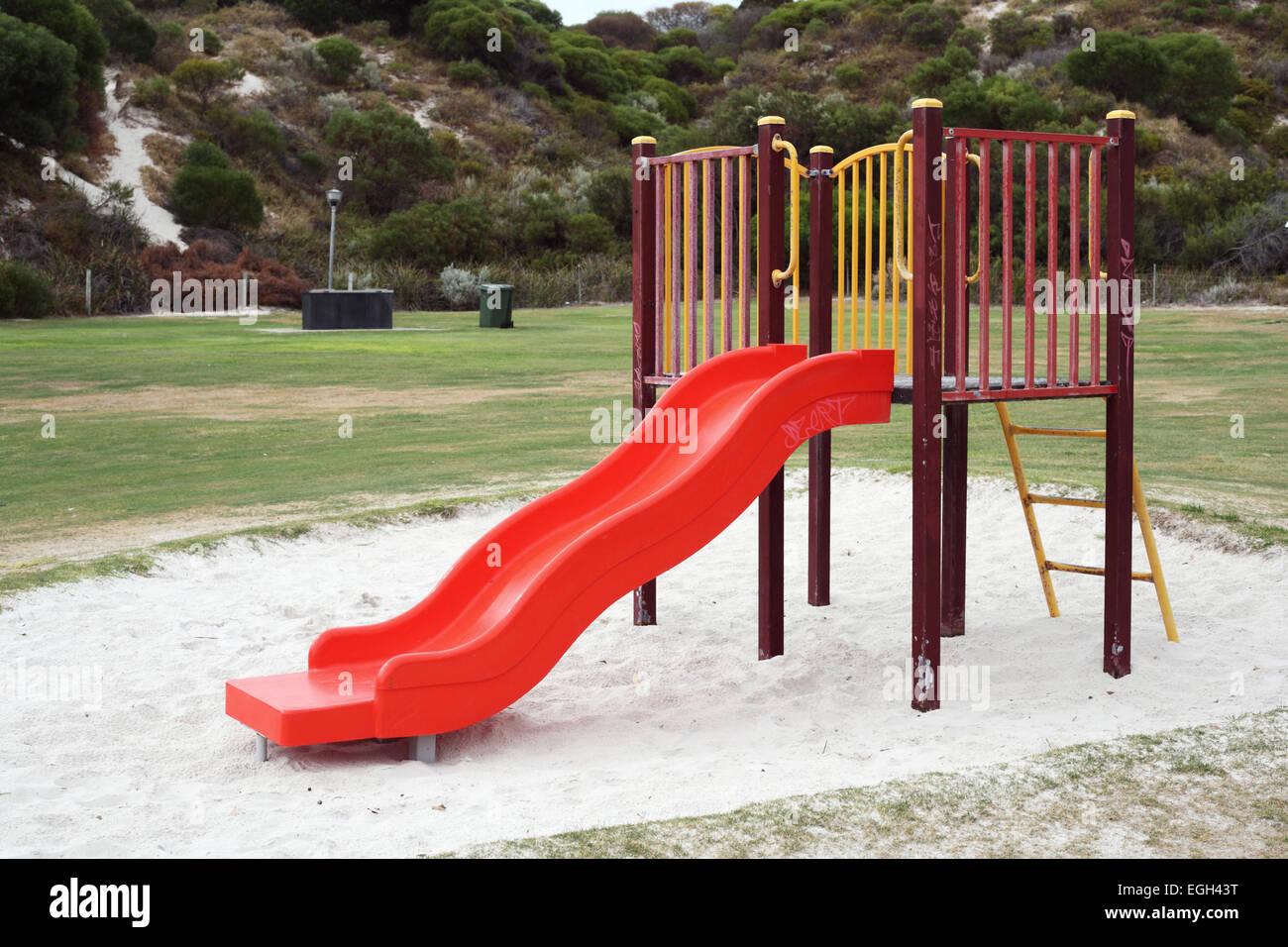 Children's playground equipment comprising a slide, walking bridge and climbing pole. - Stock Image