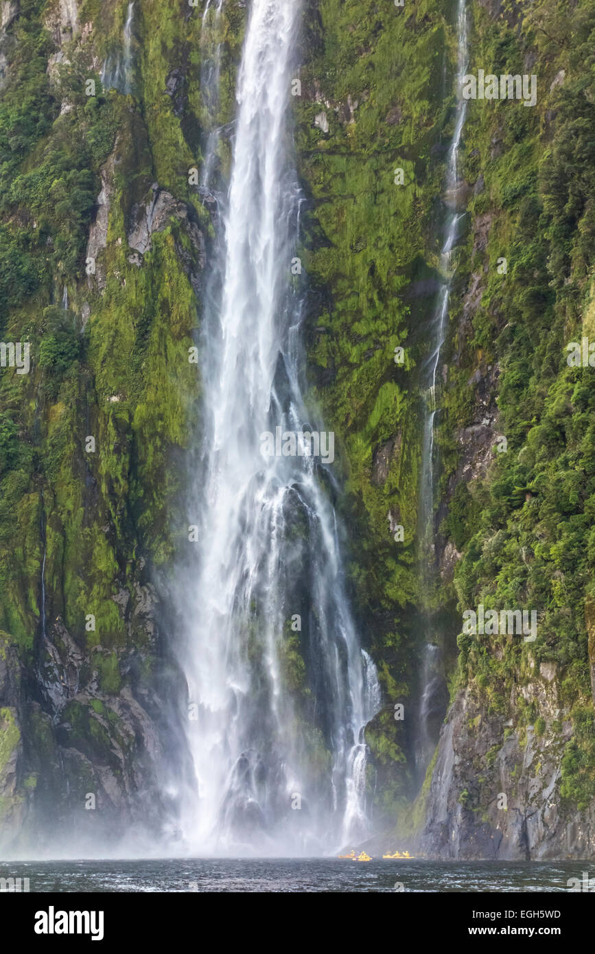 Milford Sound Stirling Falls with four small yellow sea kayaks underneath high waterfall. Fiordland National Park - Stock Image