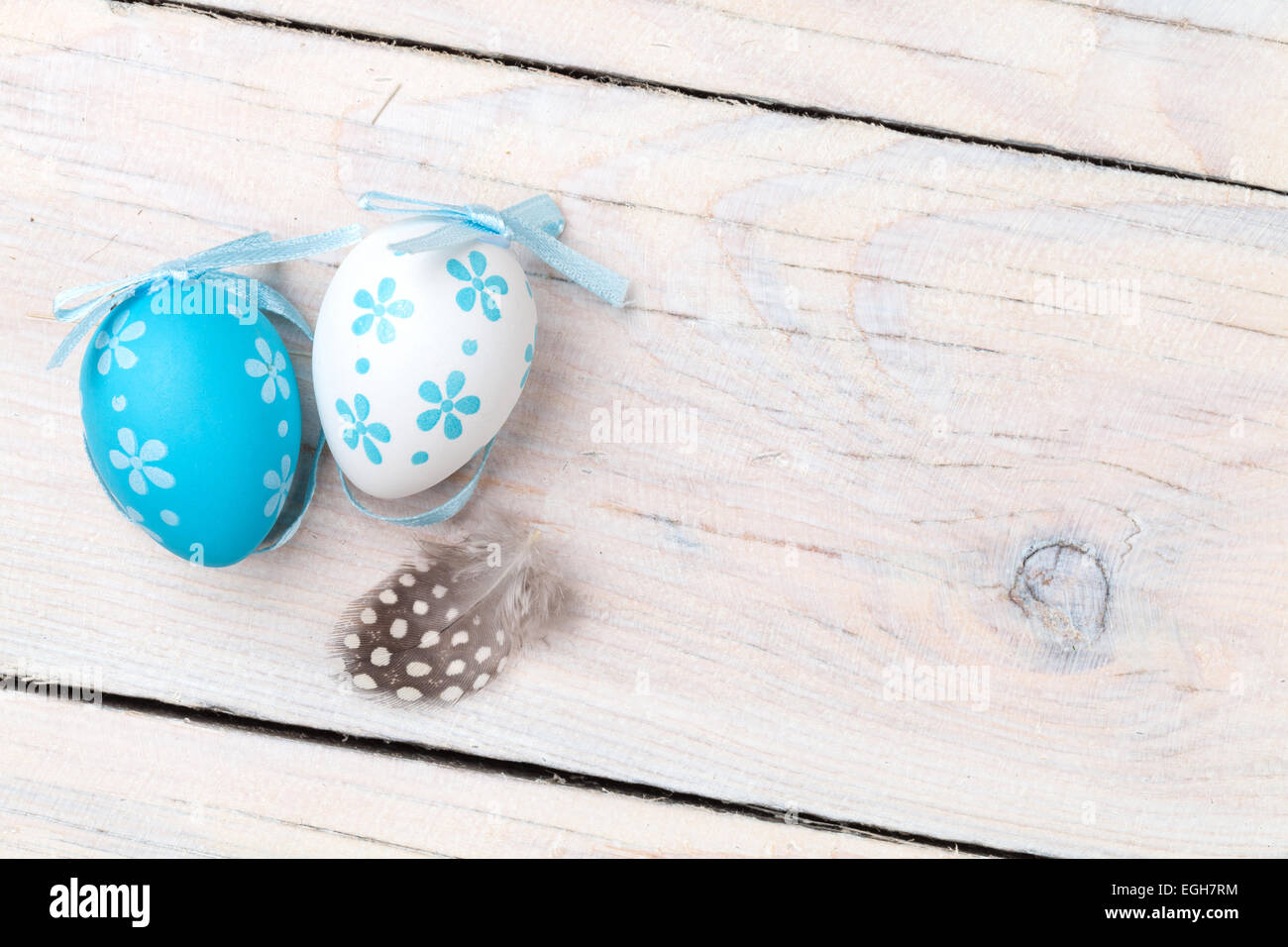 Easter background with blue and white eggs and feather over white wood. Top view with copy space Stock Photo