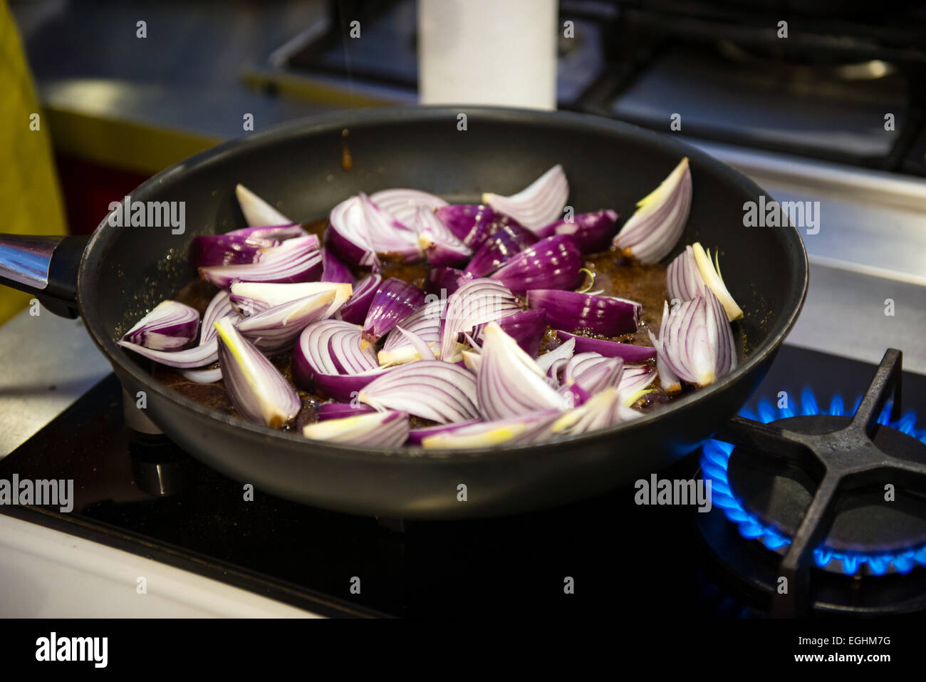Preparing steak sauce from red onion wedges, caramel and red wine - Stock Image