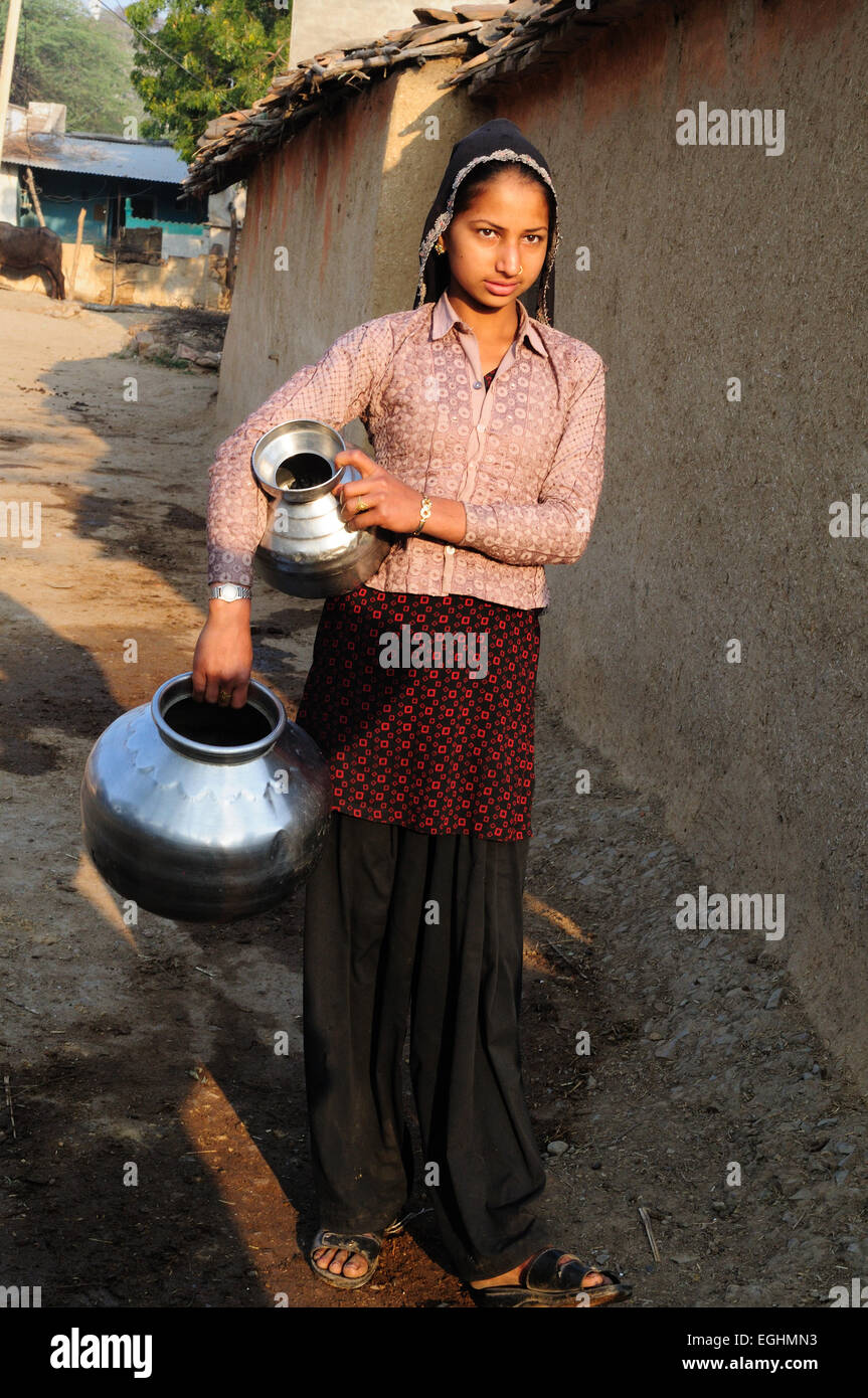 An Indian girl holding metal pots to collect water in her Tribal Village  Madhya Pradesh India - Stock Image