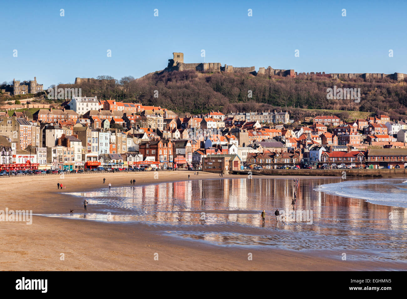 A bright winter day in Scarborough, North Yorkshire, England, UK, a view over the beach to the castle, with people - Stock Image