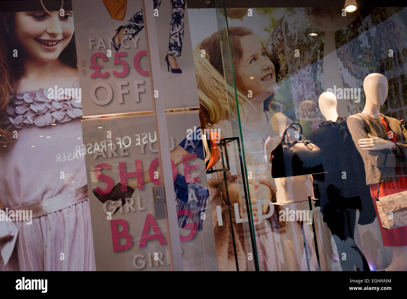 Young models in the window of a nearby fashion hoarding and Debenhams mannequins in central London. - Stock Image