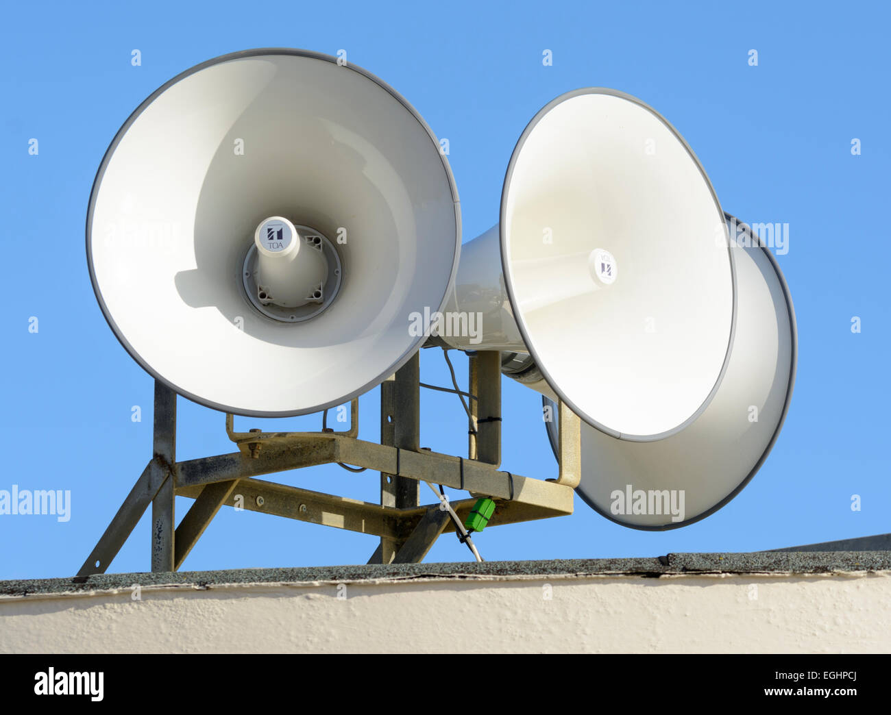 2 megaphones on top of a building as part of a public address system. - Stock Image