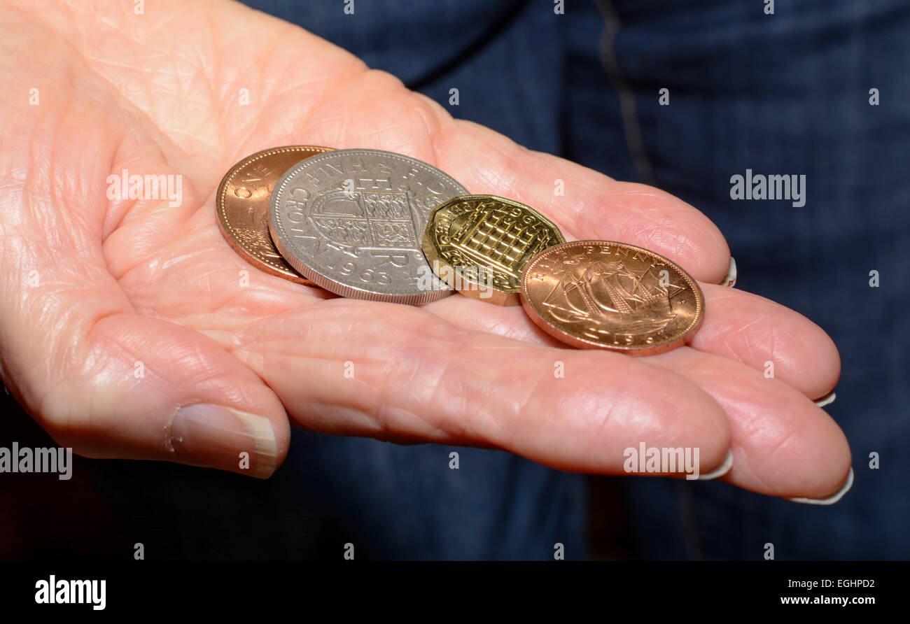 Several old pre-decimal coins in a person's hand. - Stock Image