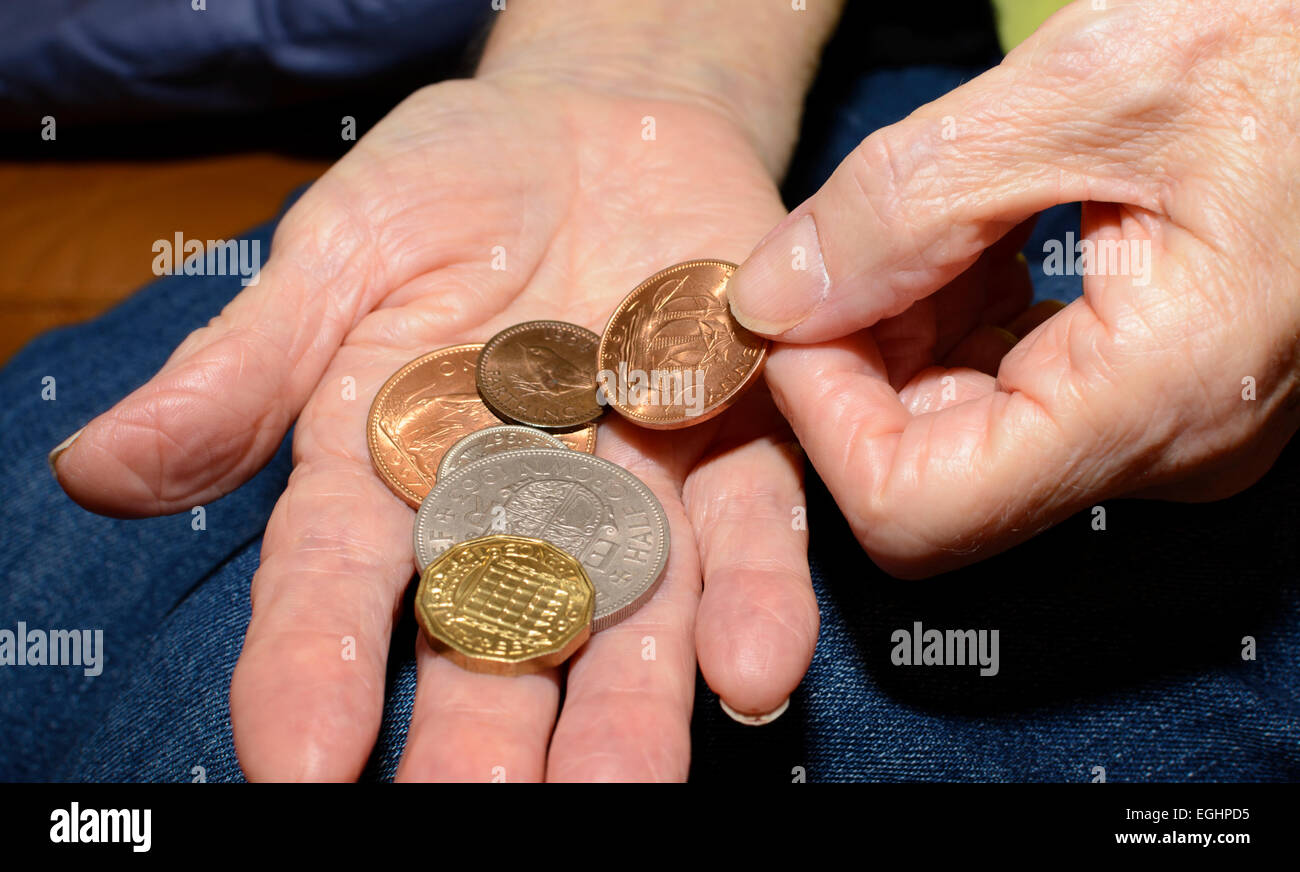Several old pre-decimal UK sterling coins in a person's hand. - Stock Image