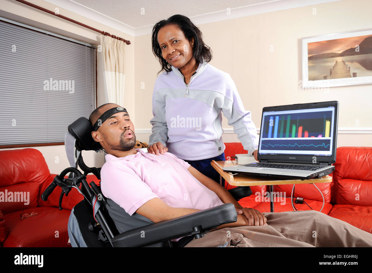 Richard Gregory has Locked-in Syndrome is pictured with a device which interprets his brainwaves. Pictured with - Stock Image