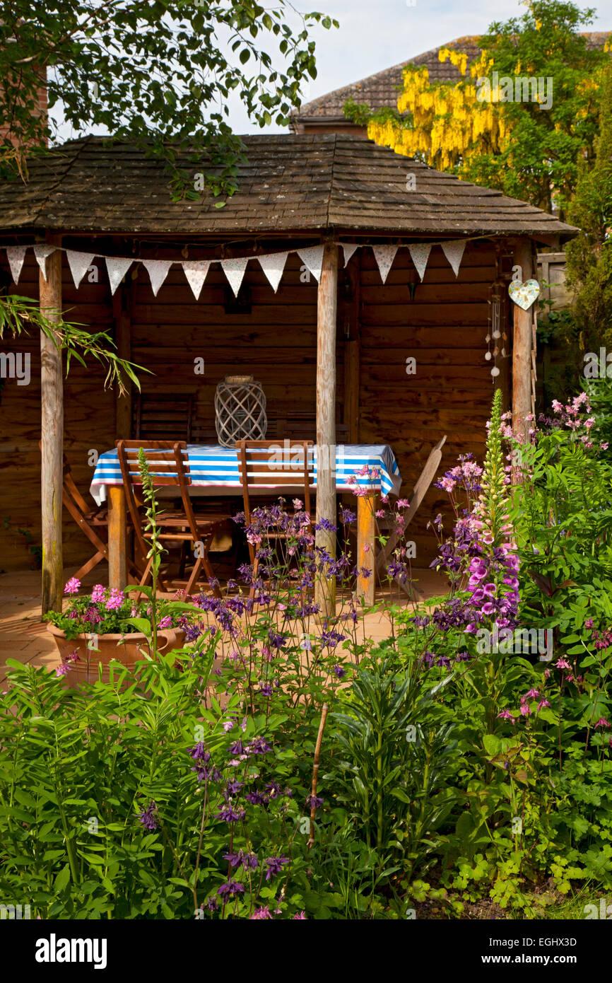 Wooden Outdoor Summerhouse in English Garden - Stock Image