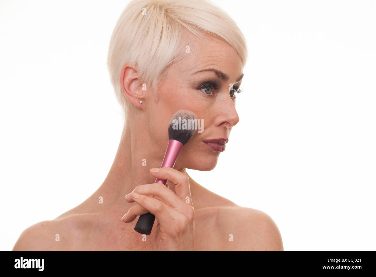 platinum blonde female in her 40s applying make up - Stock Image