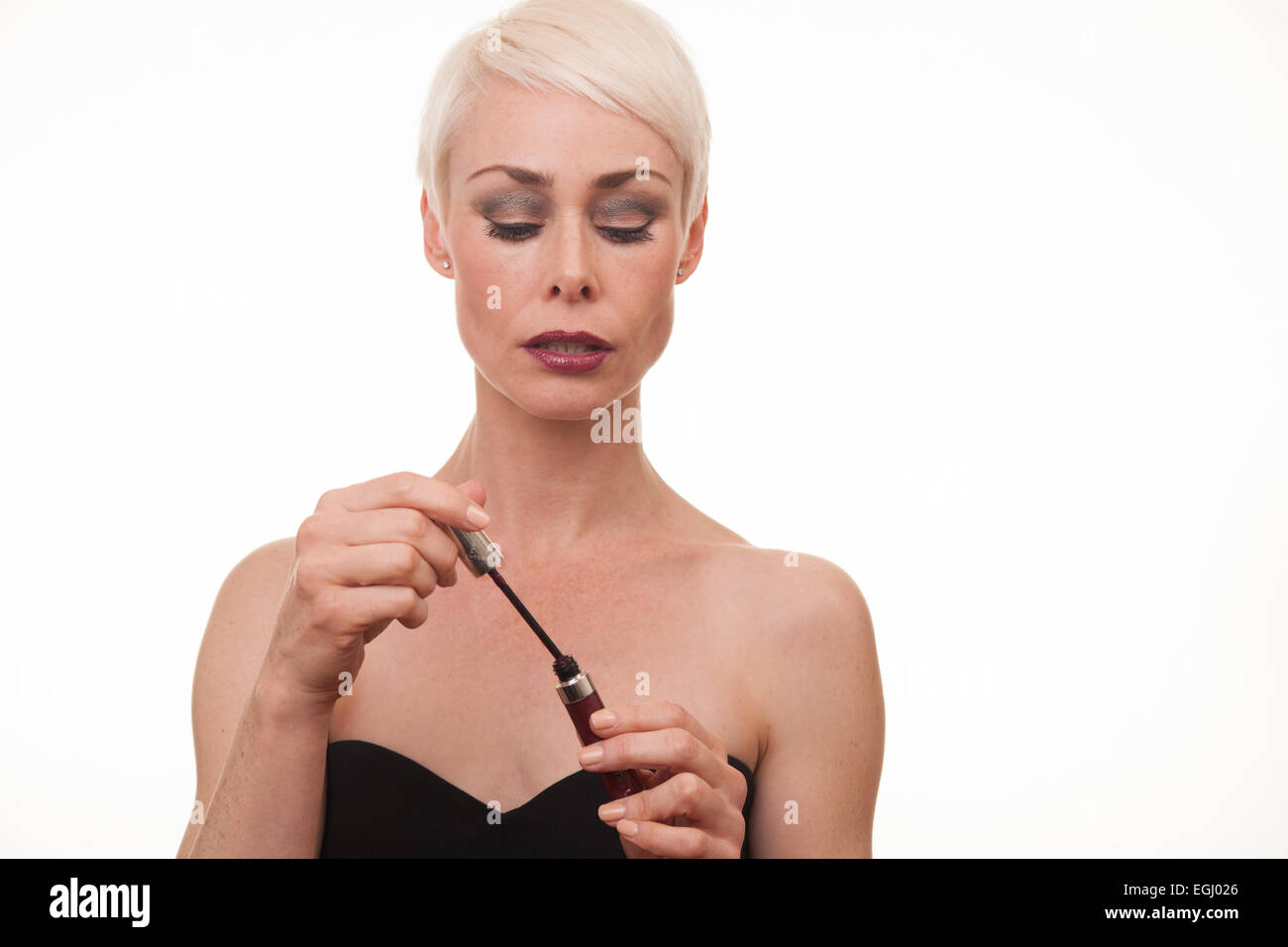 platinum blonde female in her 40s applying lipstick - Stock Image