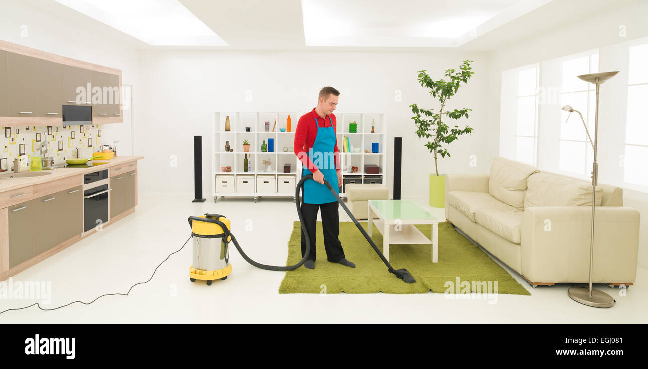 caucasian man cleaning carpet with vacuum cleaner in living room ...