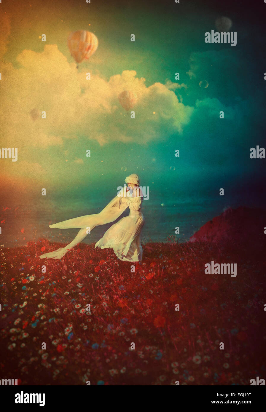young woman in white dress dancing on the cliff - Stock Image