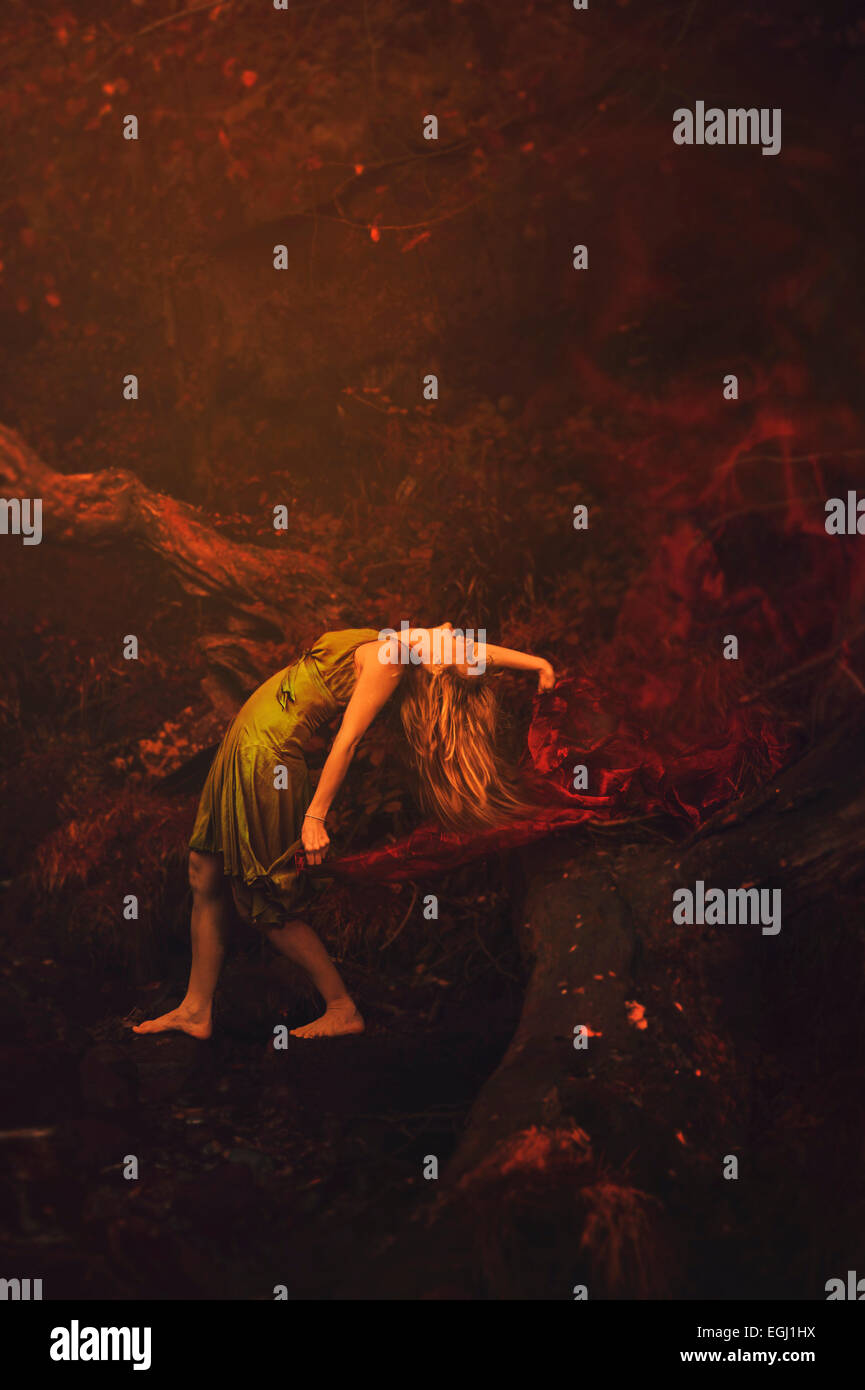 young woman dancing in nature holding red shawl - Stock Image