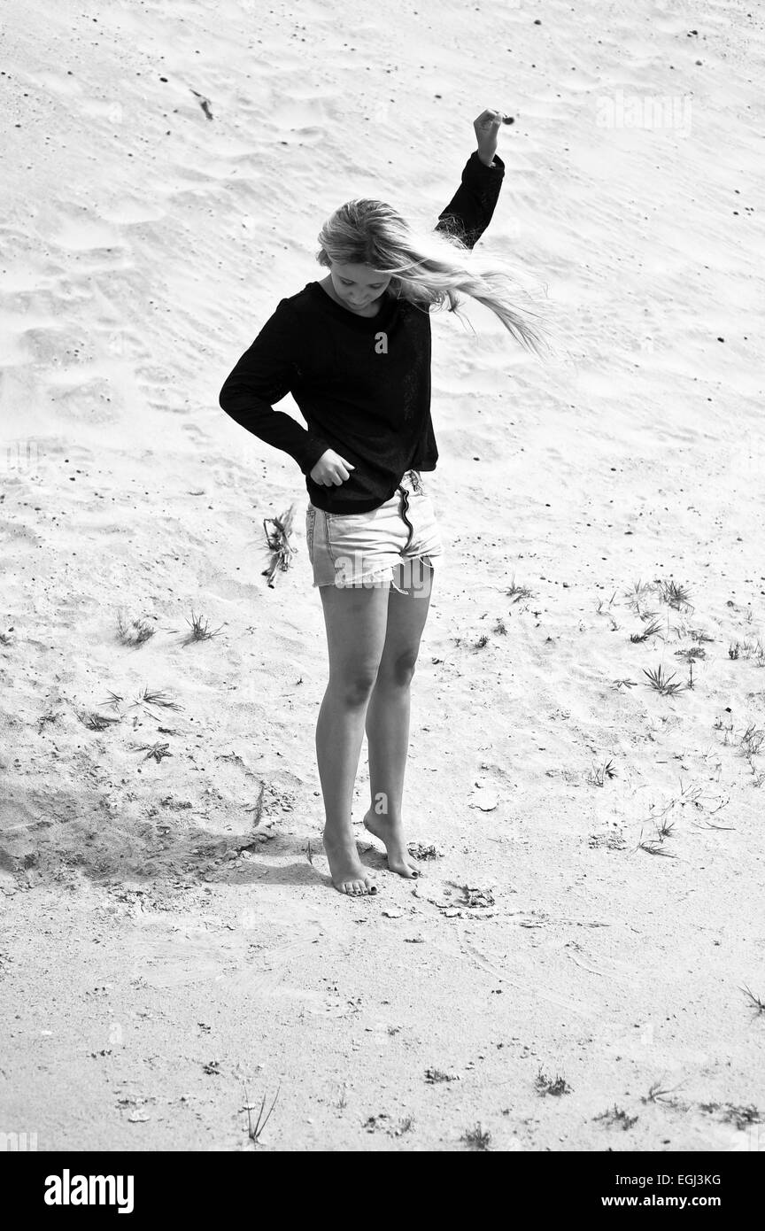 Young woman standing on tiptoe at the beach, - Stock Image
