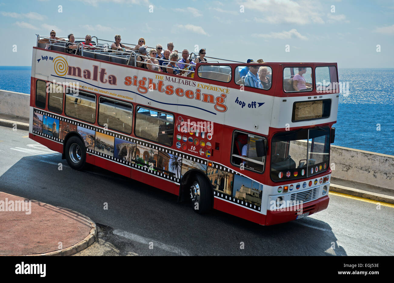 Tourists in an open-top double-decker bus on an excursion at the coast, Malta - Stock Image