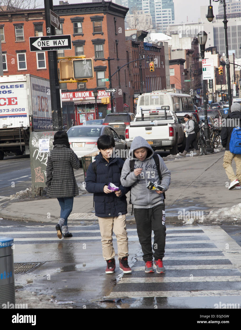 Pre-teen boys snack as they walk home after school along Smith Street in the Carroll Gardens neighborhood of Brooklyn, - Stock Image