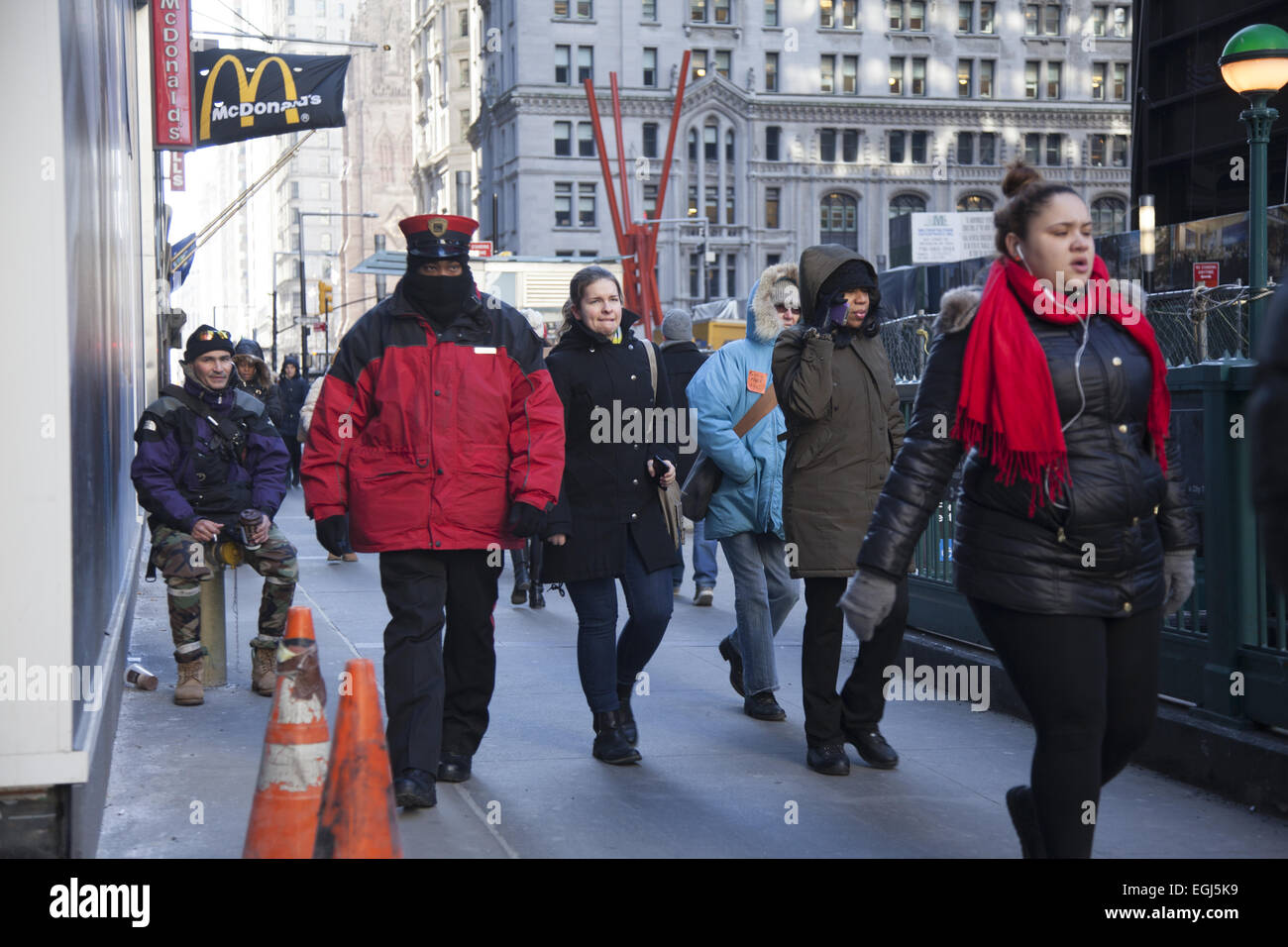 Pedestrians walk along lower Broadway in strong winds and freezing temperatures in New York City. - Stock Image
