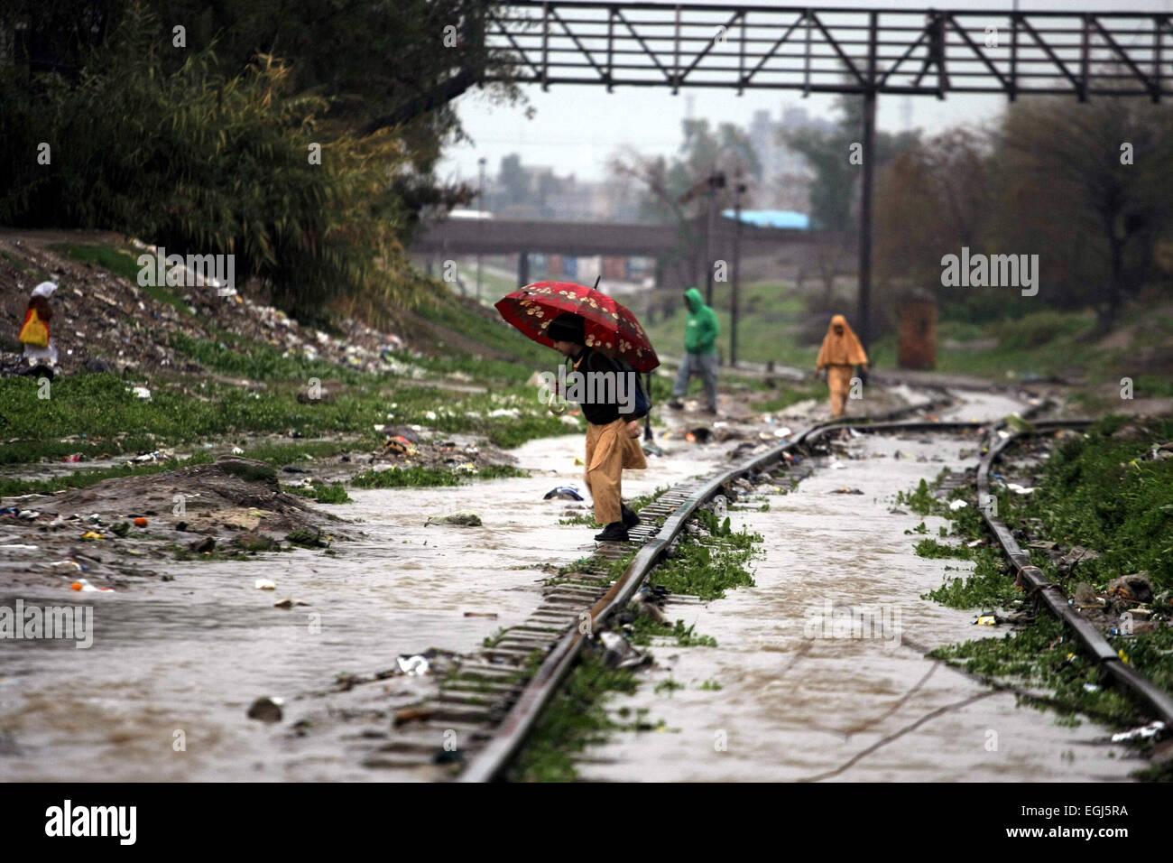 Peshawar, Pakistan. 25th Feb, 2015. A school boy crosses a waterlogged railway track after heavy rain in northwest - Stock Image