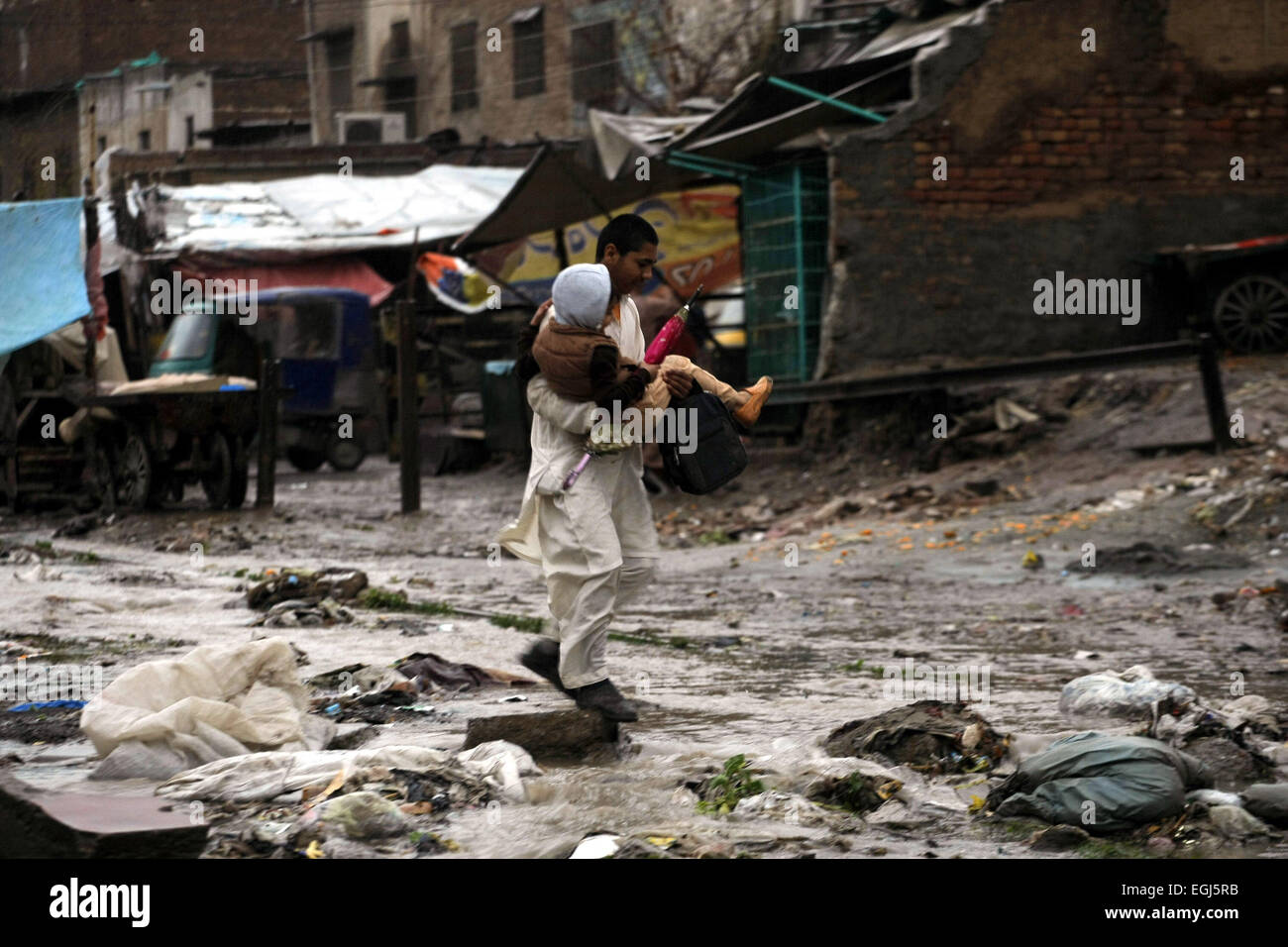 Peshawar, Pakistan. 25th Feb, 2015. A man carries a child as he crosses a waterlogged street after heavy rain in - Stock Image