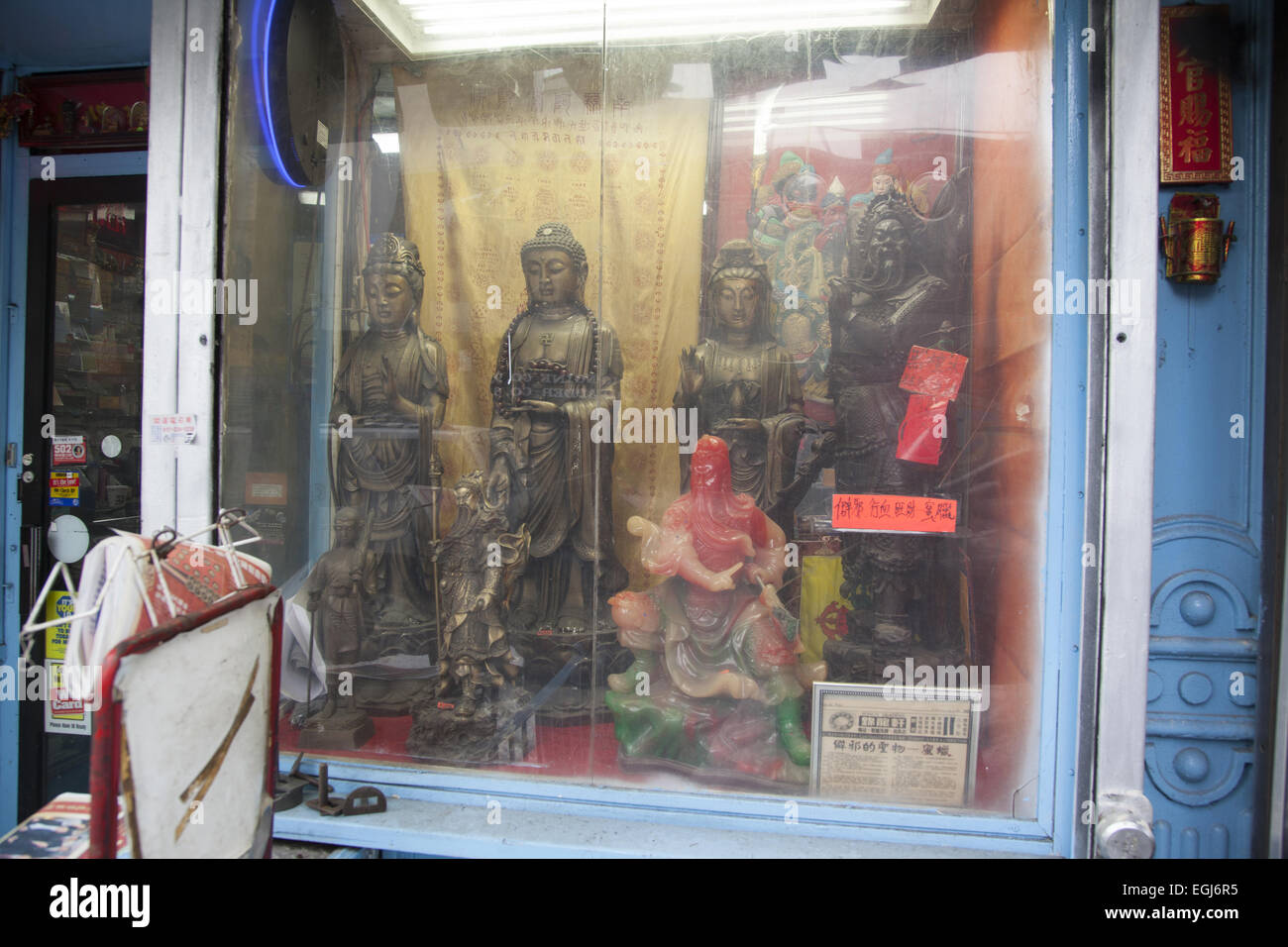 Store window in Chinatown with Buddhist & Taoist statuary. Canal Street, NYC. - Stock Image