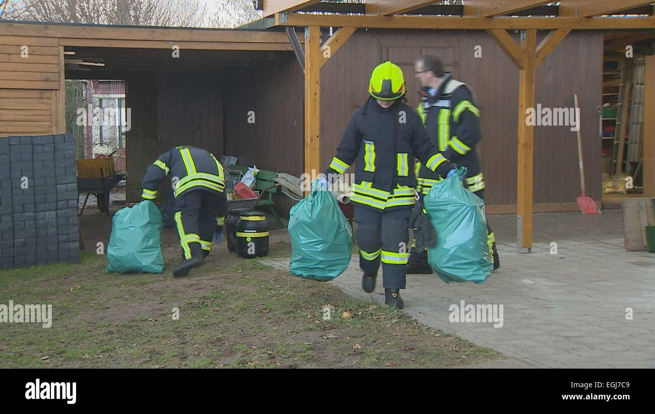 Fire fighters carry green plastic bags from a garden allotment in Preetz, Germany, 24 February 2015. A can of poisonous - Stock Image