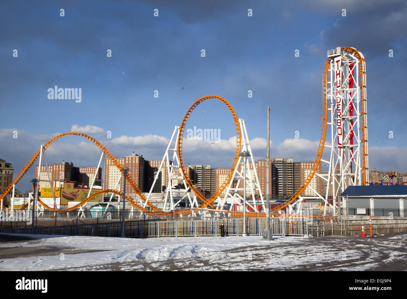 The Thunderbolt Roller Coaster stands like an abstract sculpture against the buildings and sky in winter at Coney - Stock Image