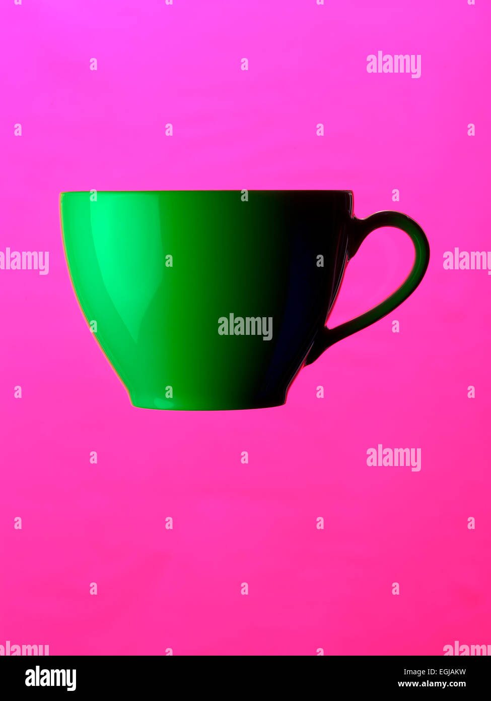 tea cup green on pink ground - Stock Image