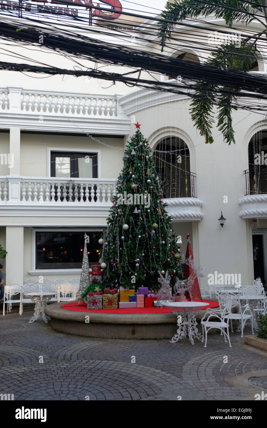 Christmas Tree outside Gulliver's Bar, Bangkok, Thailand with chaotic overhead cables - Stock Image