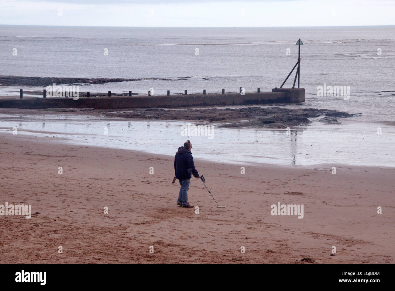 A man uses a metal detector on Exmouth beach - Stock Image