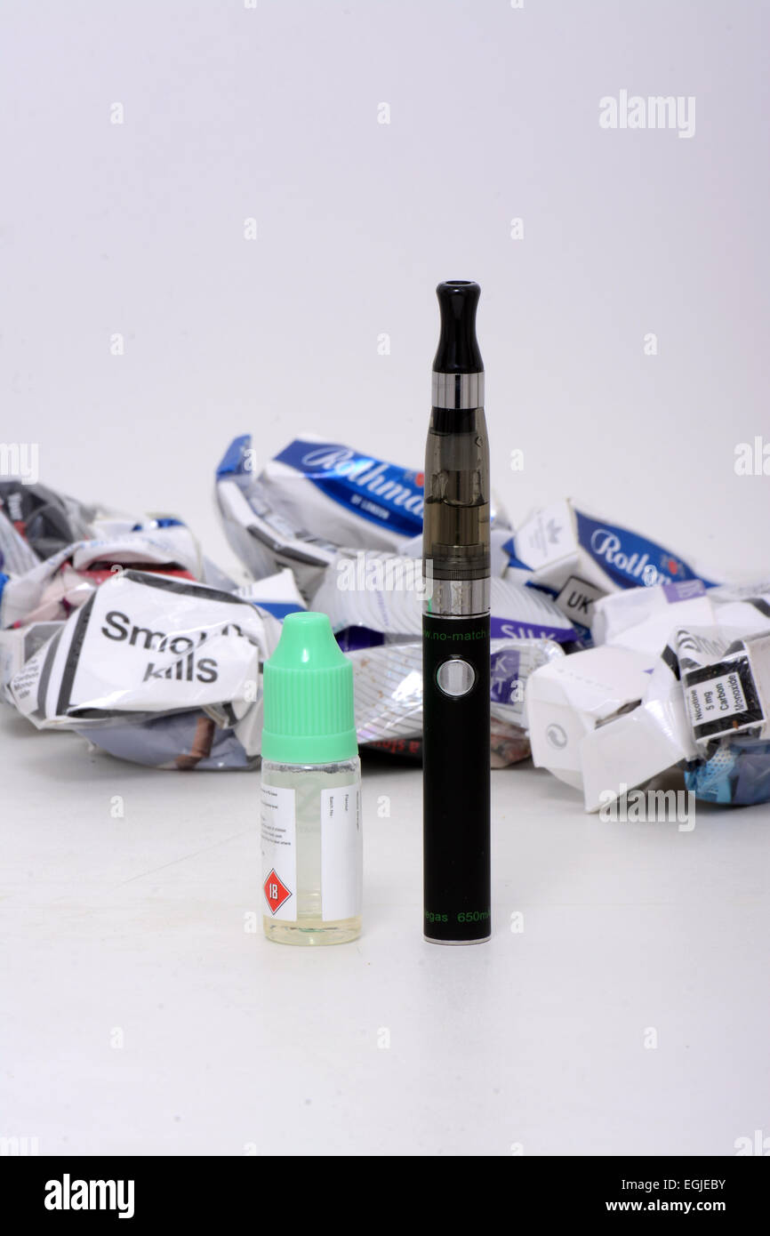 Typical e-cigarette with its fluid in front of discarded crumpled cigarette packets cartons in the background. - Stock Image