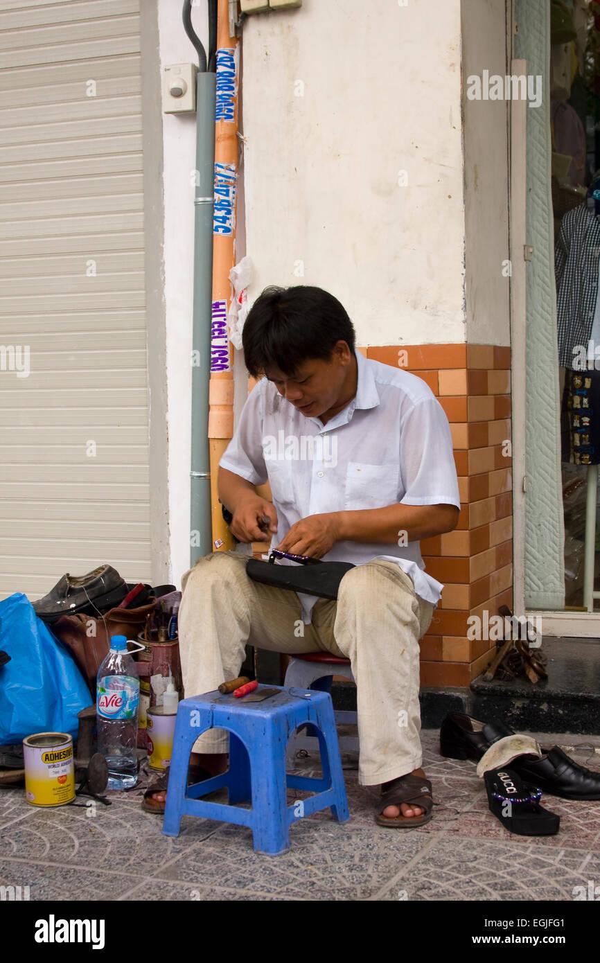 Street shoemaker repairing shoes, Saigon, Ho Chi Minh City, Vietnam, Asia Stock Photo
