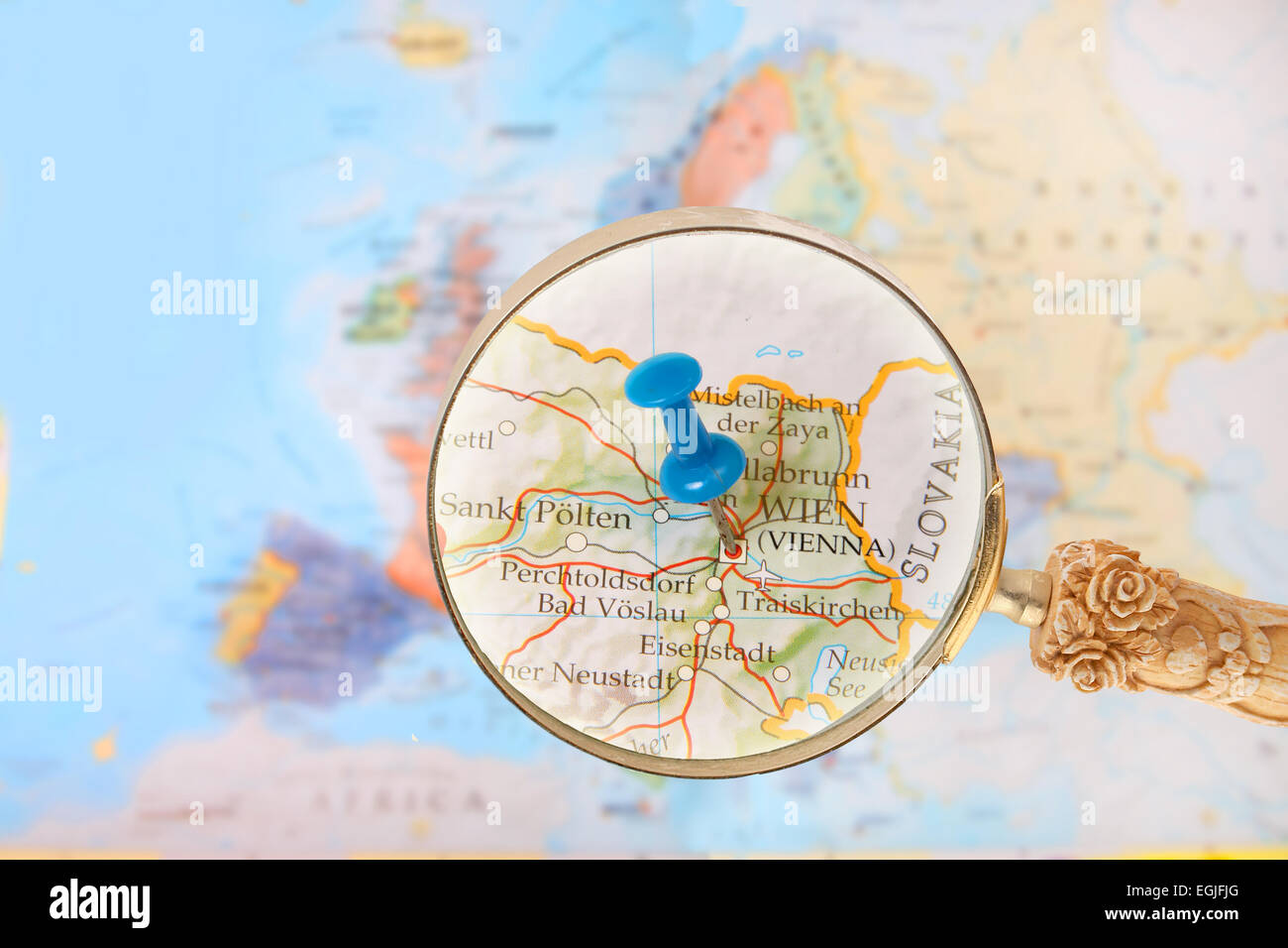 Blue Tack On Map Of Europe With Magnifying Glass Looking In On Stock